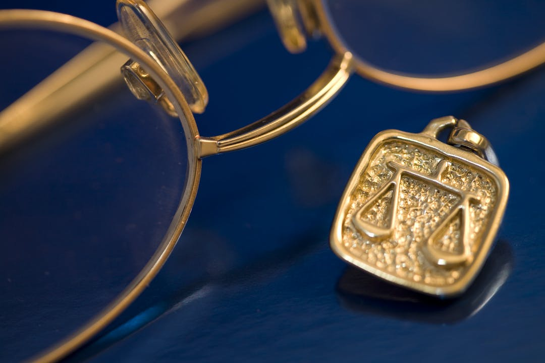 image of gold spectacles and golf ingot of scales.