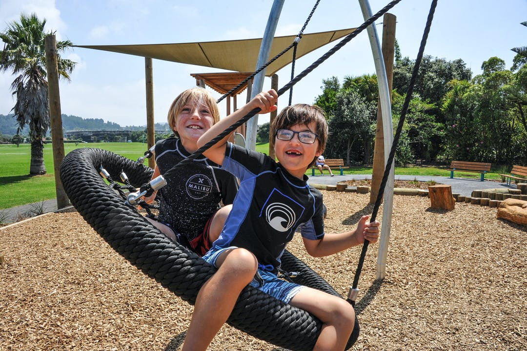 Two children on a swing at a playground