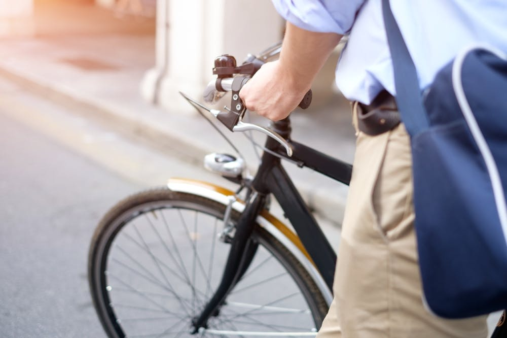 Photograph of man walking his bike