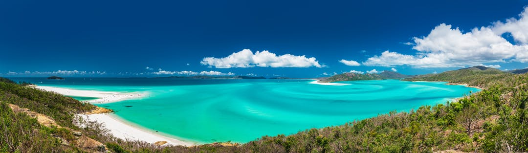 Panoramic view of Whitehaven Beach in the Whitsunday Islands, Queensland, Australia showing white sand and clear blue water