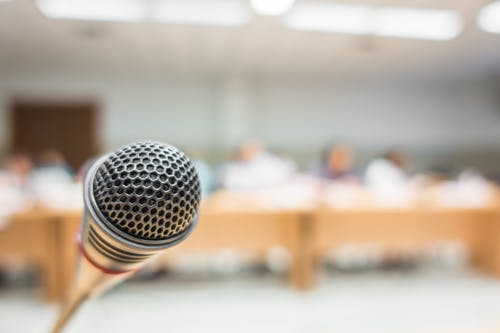 Microphone, people sitting at a row of tables in the background