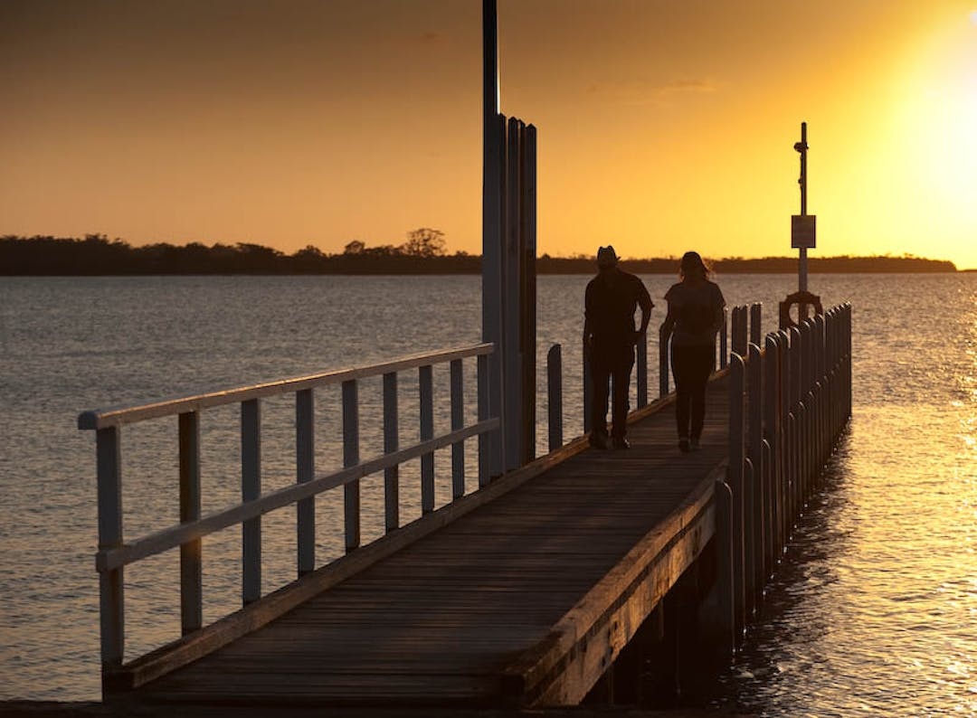 An image of two people walking along the jetty at Lake King beach, Metung at sunset