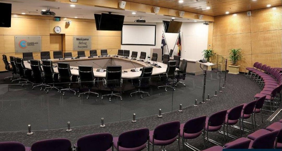 Photo of Cumberland City Council Chambers in Merrylands, with doughnut-shaped table with chairs for Councillors and senior staff and auditorium of seats for community members