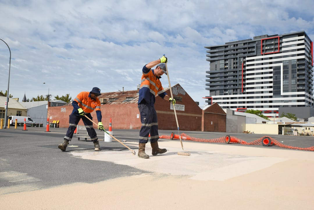 Two tradespeople applying a light coloured paint product on a road surface.