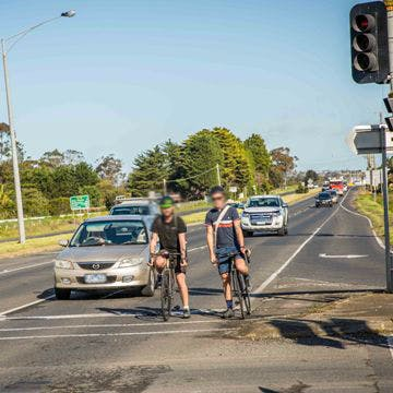 Cyclists and cars waiting for a red light in the bellarine highway