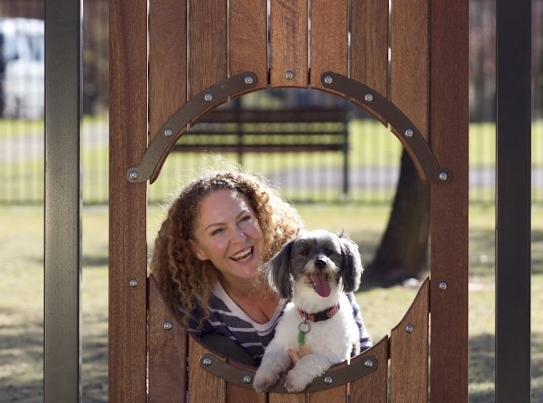 a woman with curly hair at the dog park with her small grey & white dog, they are looking through a round opening in the dog play equipment