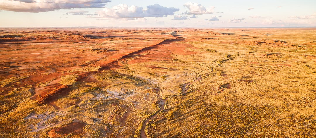 Aerial photograph of Australian outback and dry riverbeds surrounded by gum trees and Spinifex.