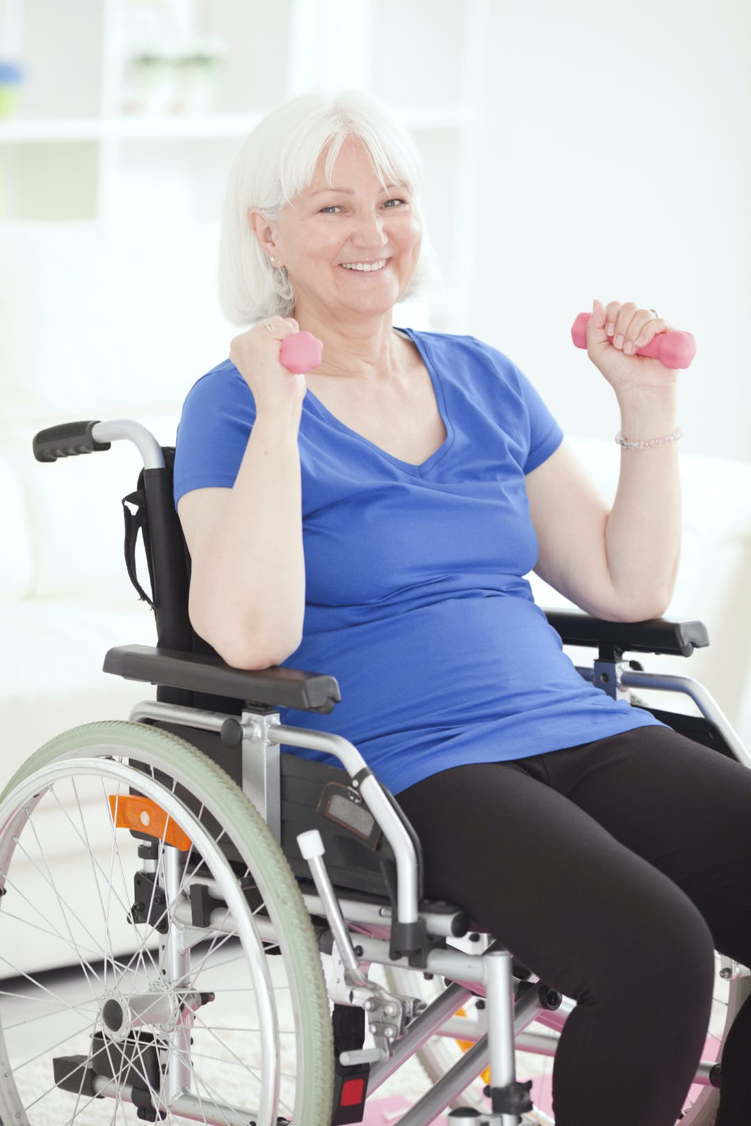 woman in wheelchair doing weights excercise