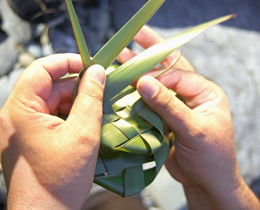 A close up of a person weaving harakeke