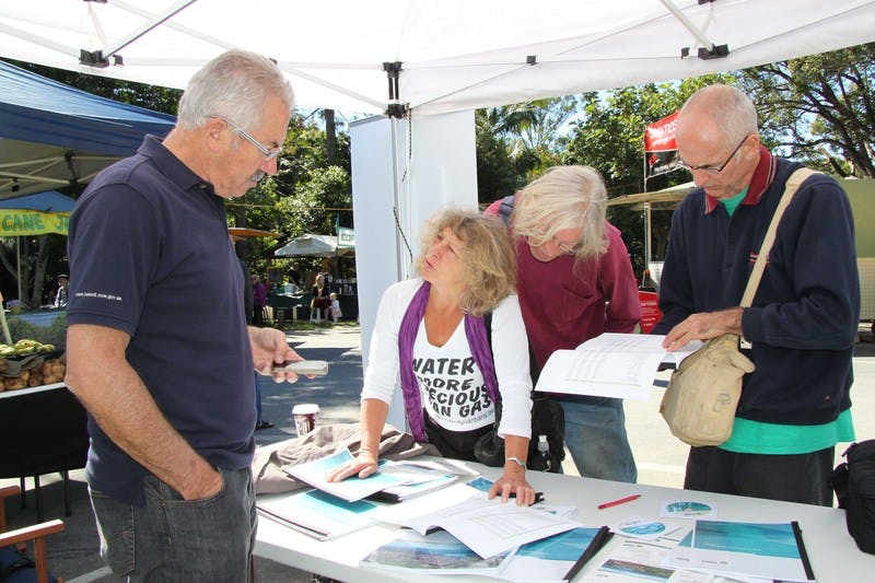 General Manager Mike Rayner (left) listens to the comments of Byrrill Creek residents Joanna Gardener and Pete Symons and Uki Village and Residents Association representative Philip Carr, at the Uki Markets community information stall.