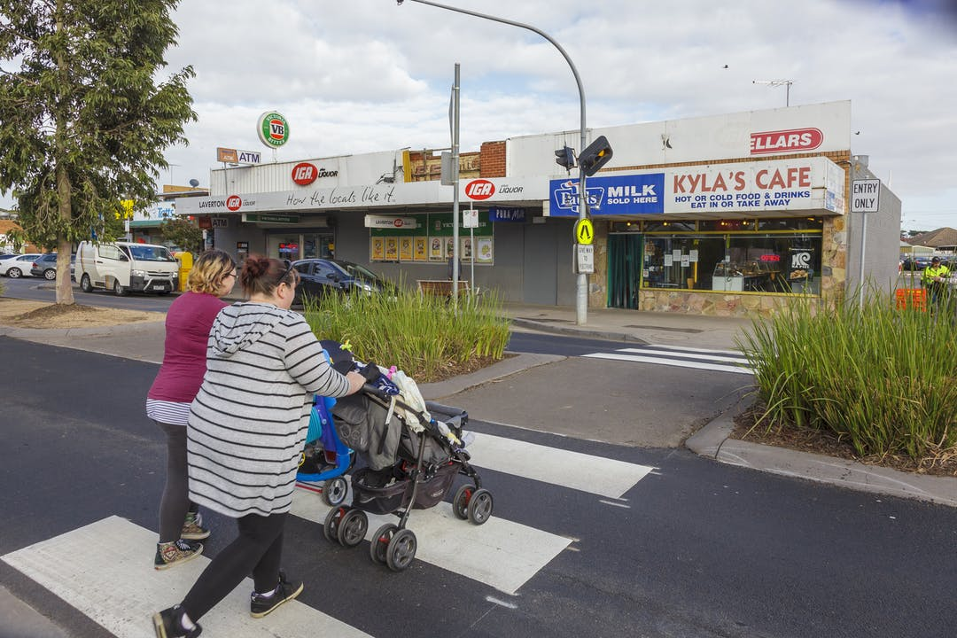 A women pushing a pram, walking beside a child along a footpath and two men riding riding bikes on a roadway with a car behind them.