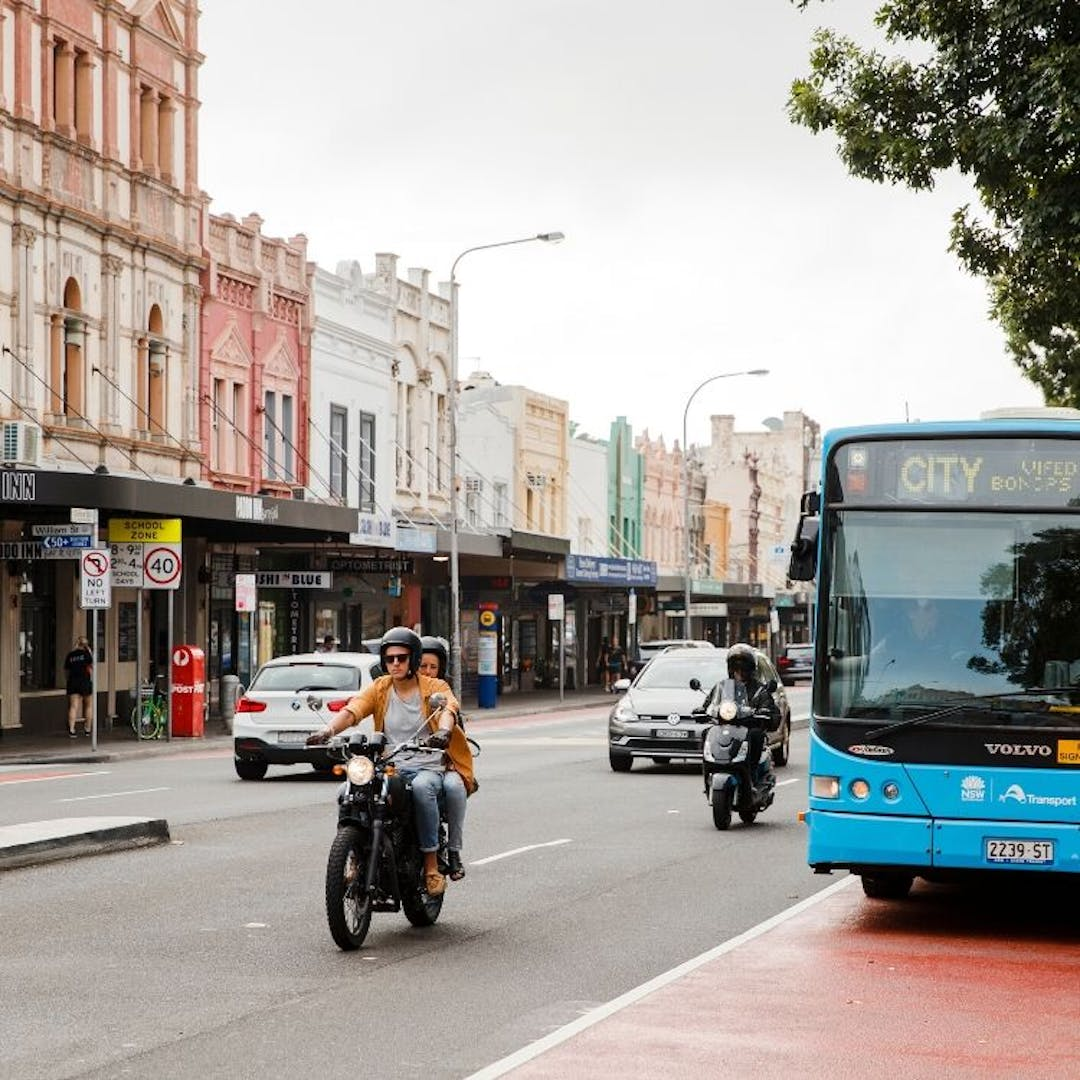 Image of a bus in a red bus lane on Oxford Street in Paddington. Other vehicles on the road include two motorcycles and a compact car. In the background, there are pedestrians walking on the pavement.