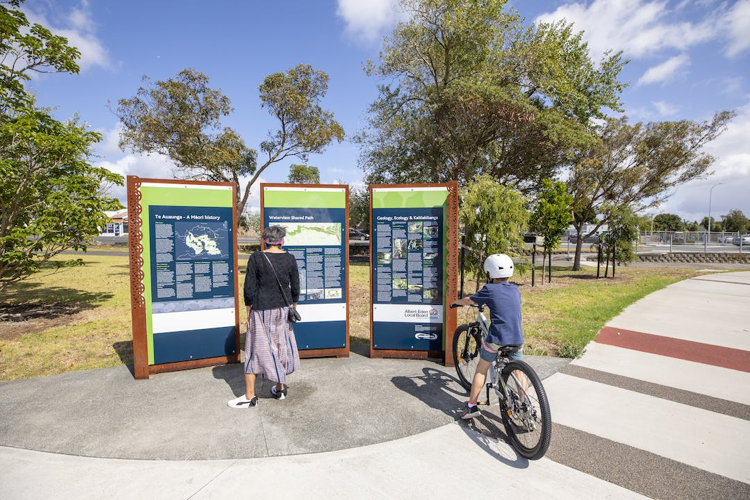Woman and boy on a bike looking at signage and information at the start of the shared path in Waterview