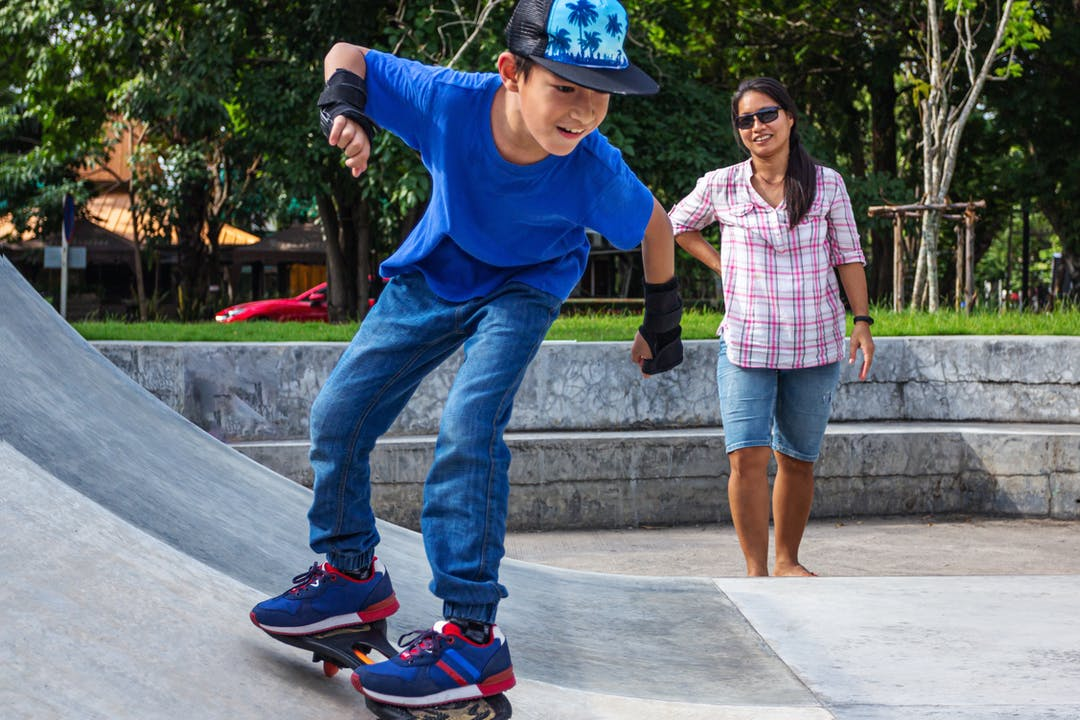 Boy skating on half pipe with parent
