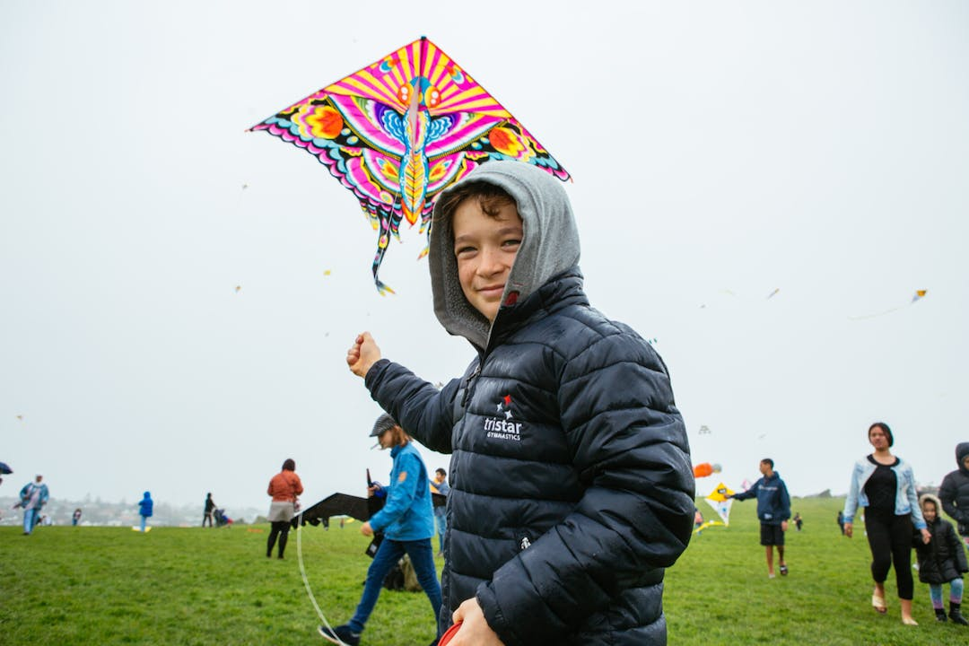 A child holding a kite at Matariki Kite Day with lots of people flying more kites in the background