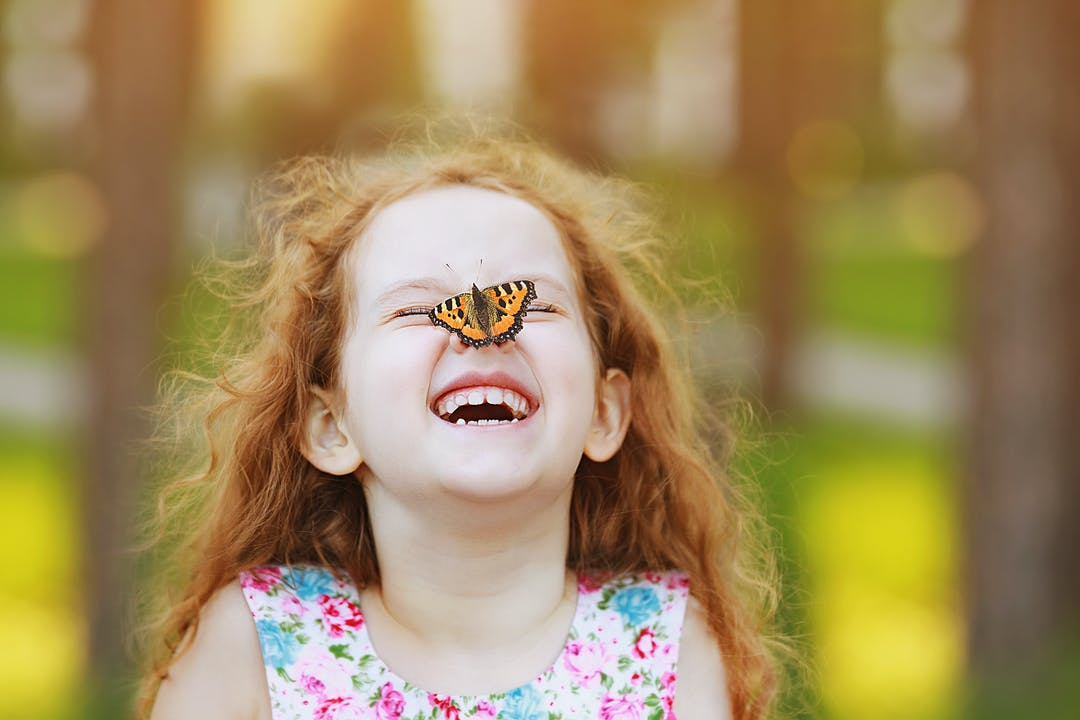 Child laughing with butterfly on nose