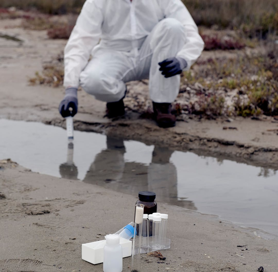 A person wearing a protective plastic jumpsuit and gloves is testing water in a muddy field using a glass beaker
