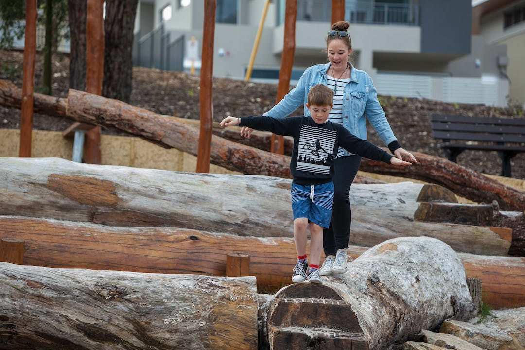 Adult and child balancing on a log