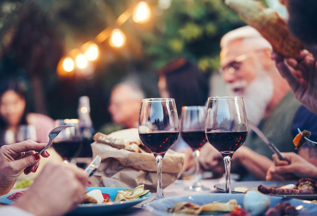 Image of people talking, laughing and enjoying dinner outdoors.