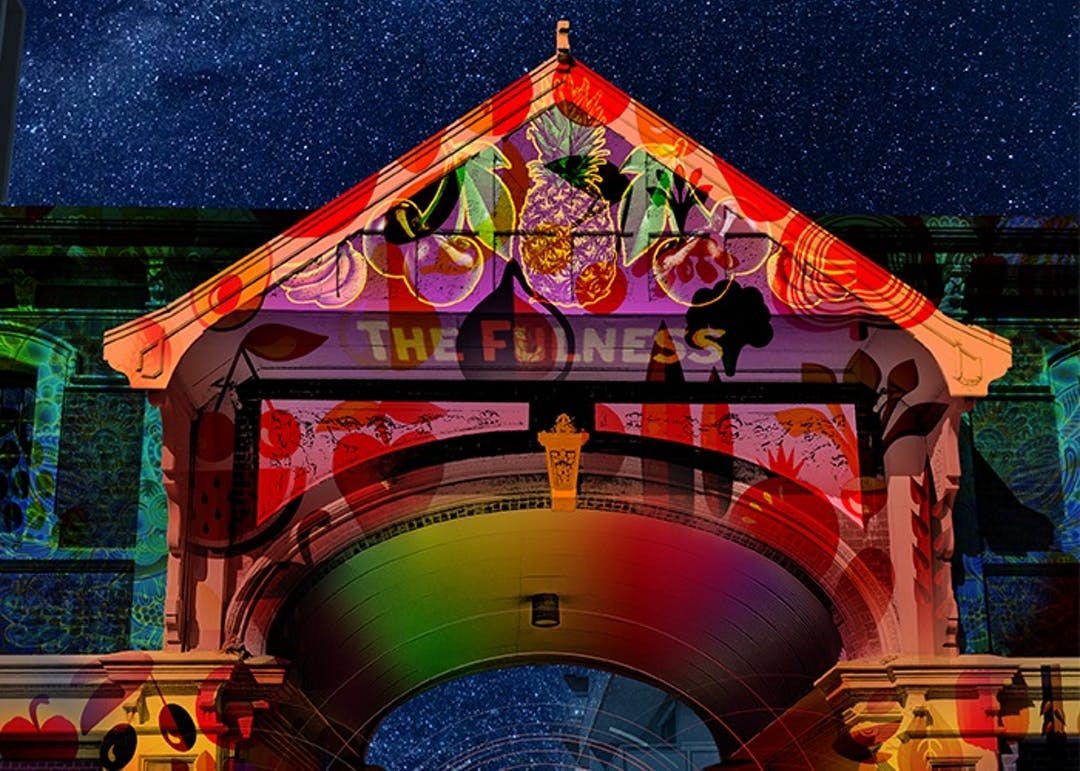 Projection of an image of arched gateway on to the wall of a building. The arched gateway appears red and orange and is ornately decorated with fruit patterns (pineapples, bananas and cherries) and is set against a backdrop of a bright starry sky.  The image will be part of 'East End Echoes' one of a series of light displays for 'Illuminate Adelaide'. Illuminate Adelaide is a celebration of innovation, music, art, light and technology at many sites in the City of Adelaide.