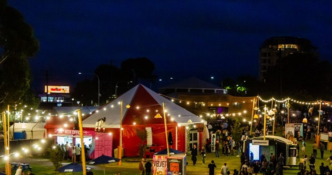 This is a vibrant view of Gluttony after dark. Clearly visible are the Gluttony Box Office and Information Kiosk. There lots of people milling around this well-lit scene.