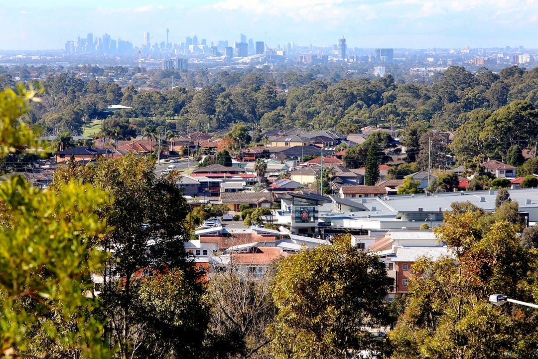 View of housing in Pemulwuy from Prospect Hill, with trees amongst the houses and skyscrapers in Sydney CBD in the background.