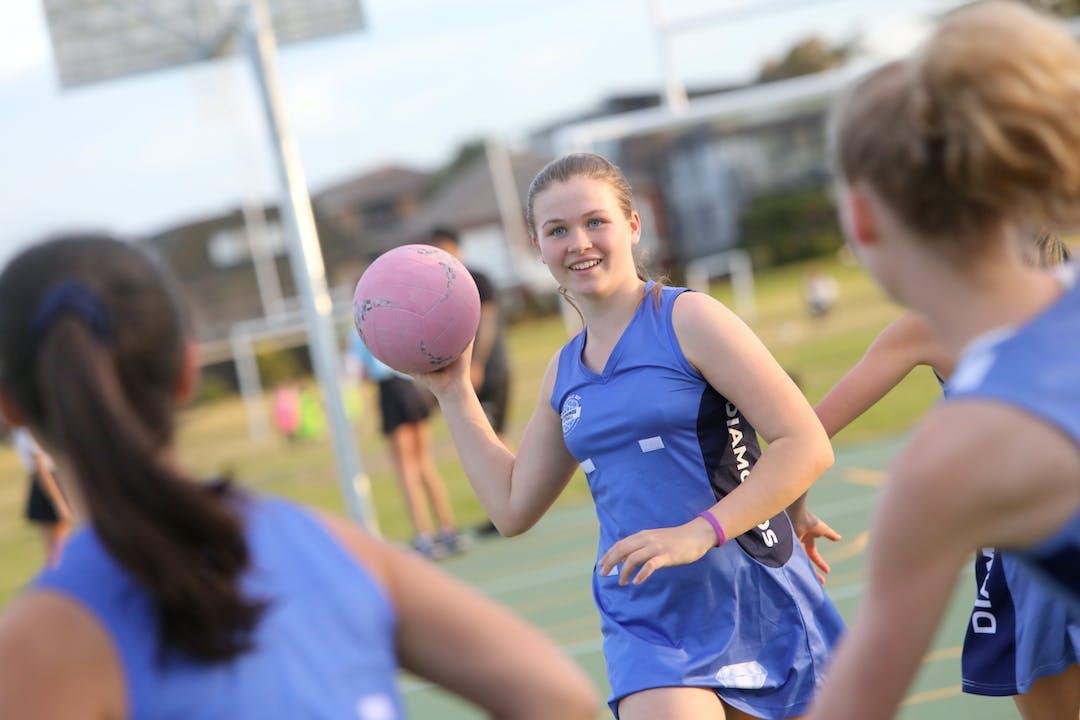 Teenage girls playing netball
