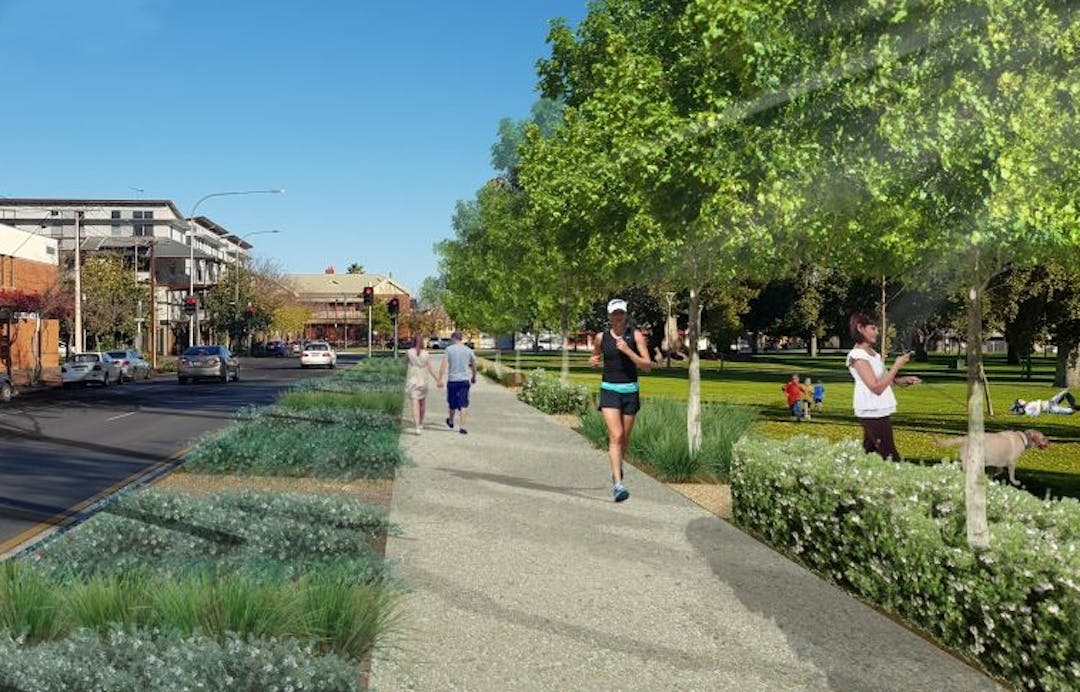 Artist's impression of Whitmore Square depicting a shared pathway lined with additionally planted trees. On the pathway you can see a jogger coming towards you and, in the medium distance, a young couple walking hand -in- hand away from you.  Also visible in Whitmore Square are a lady walking her dog and people relaxing on the grass.