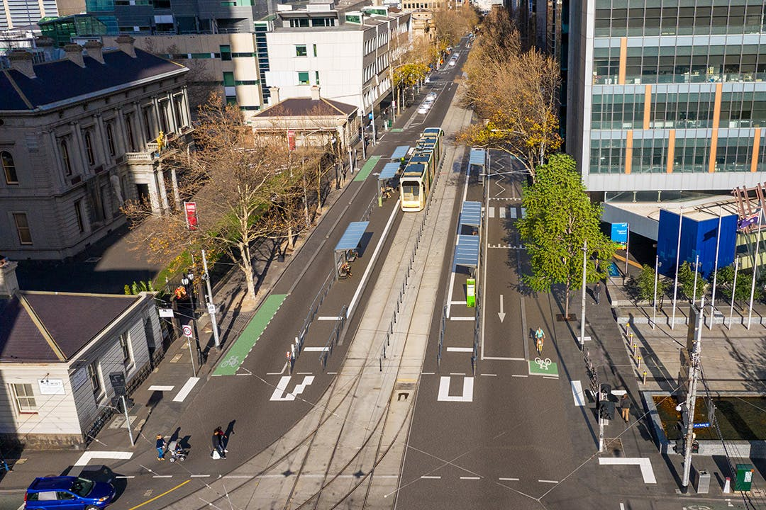 A tram stands in a computer-generated render image of La Trobe and William Street. New tram stop infrastructure, tram stop platforms, the Mint Building, as well as other buildings along William Street can be seen. The sun is directly behind the camera, to the north. Some cars are in the road in the foreground, in La Trobe Street.