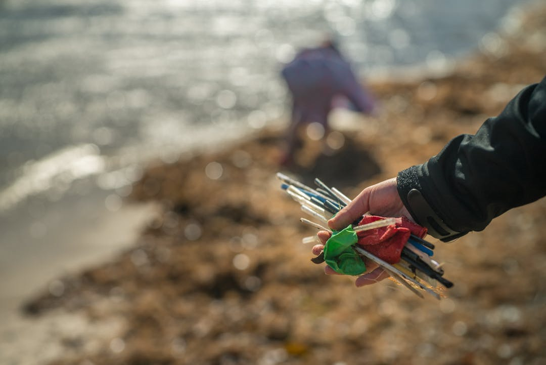 Image of a hand holding plastic and rubbish collected from the beach.