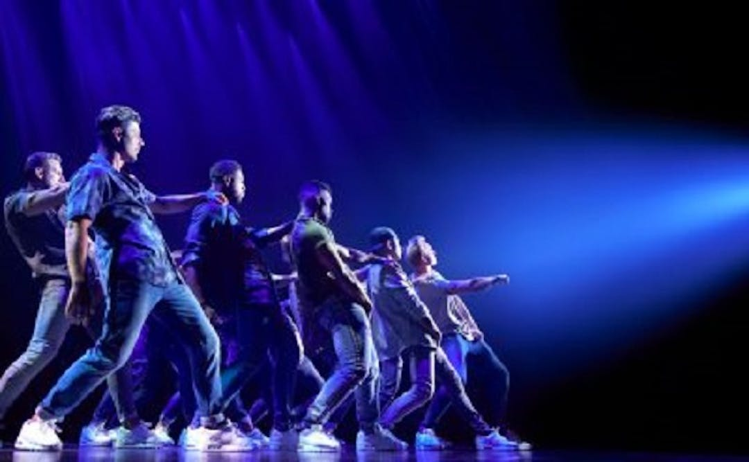 Six young male dancers dancing on a stage. The stage is lit blue with a blue/white spotlight shining on the dance group.