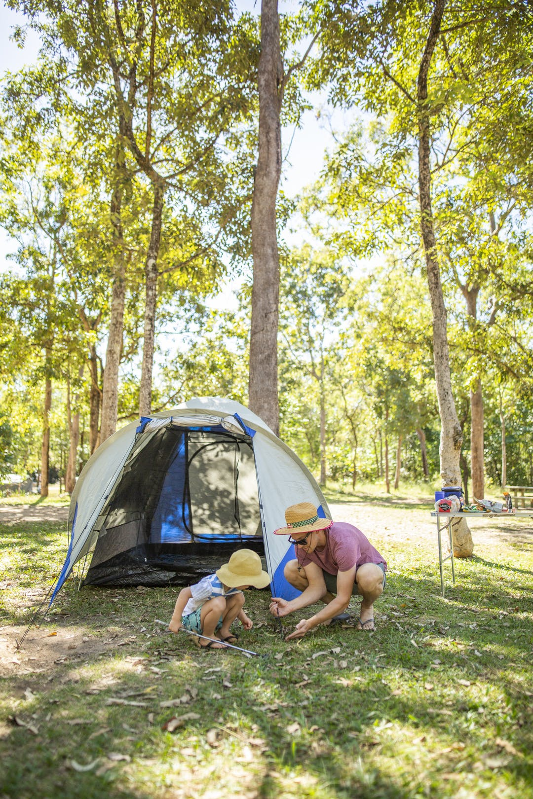 Father and son playing in campgounds outside of a tent