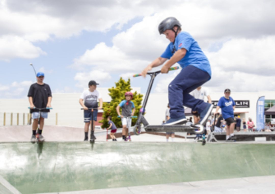 Children riding their scooters in a half pipe at the opening of the new Pukekohe Skate Park.