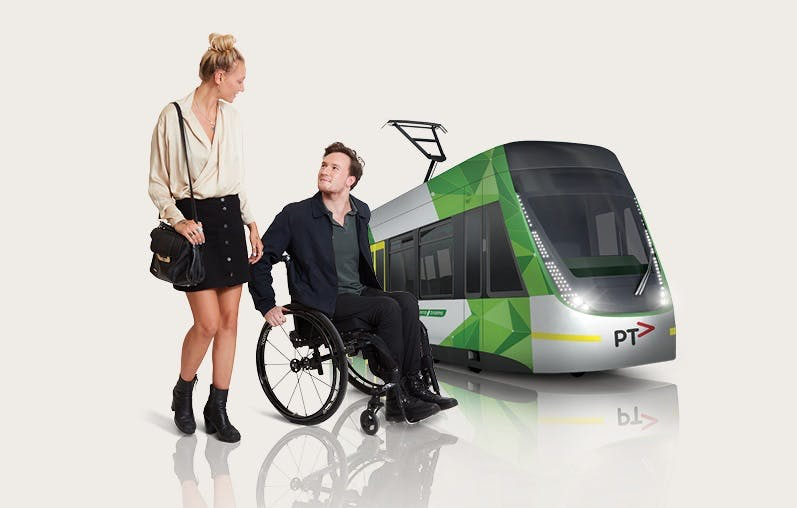 Picture of a low floor e-class tram in the background with a woman and man using a wheelchair in the foreground.