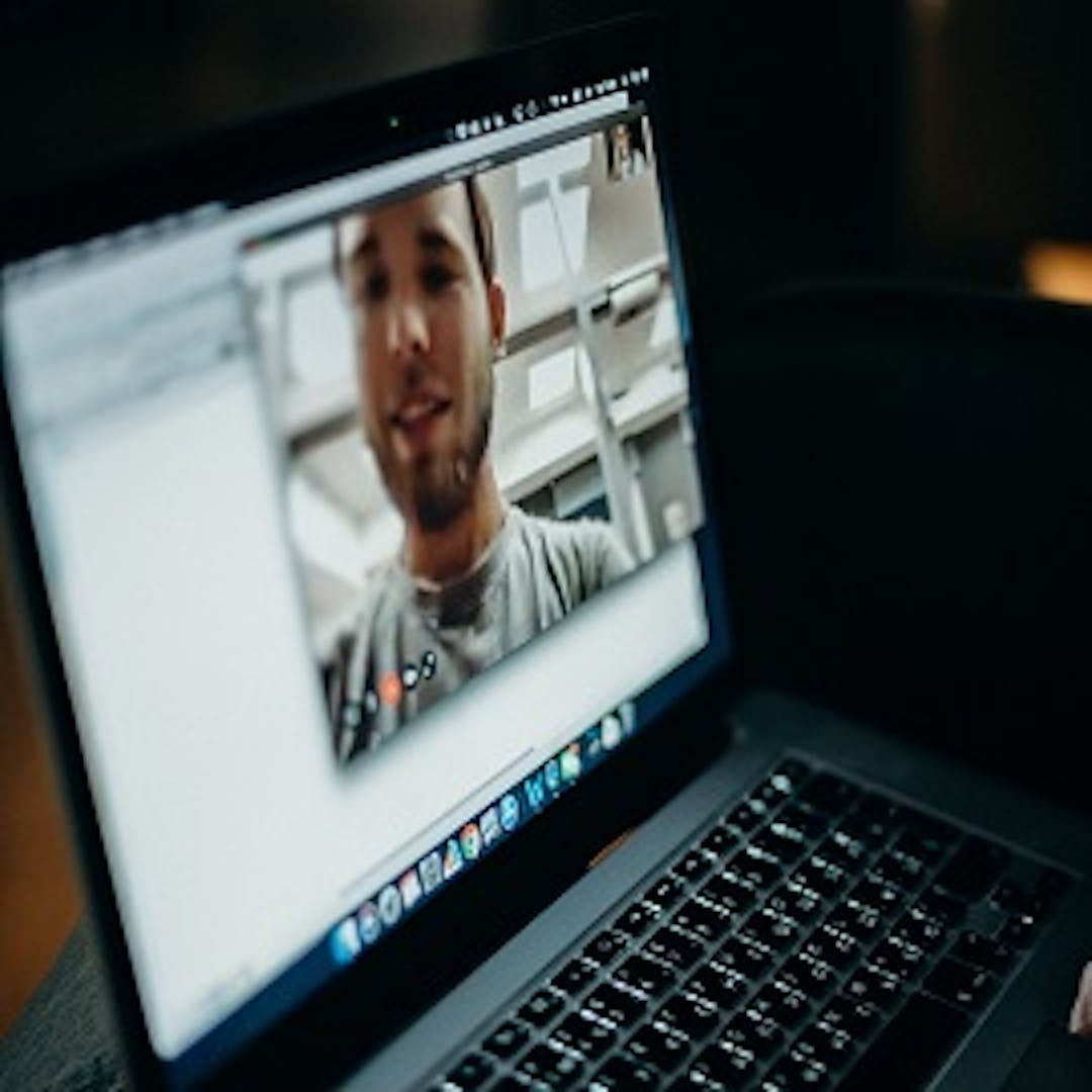 An open laptop sits on a desk in a darkened room.  A window on the laptop shows a young man catting on a teleconference.