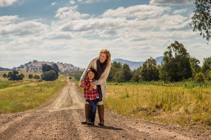 lady standing holding child infront on country road with hill landscape background