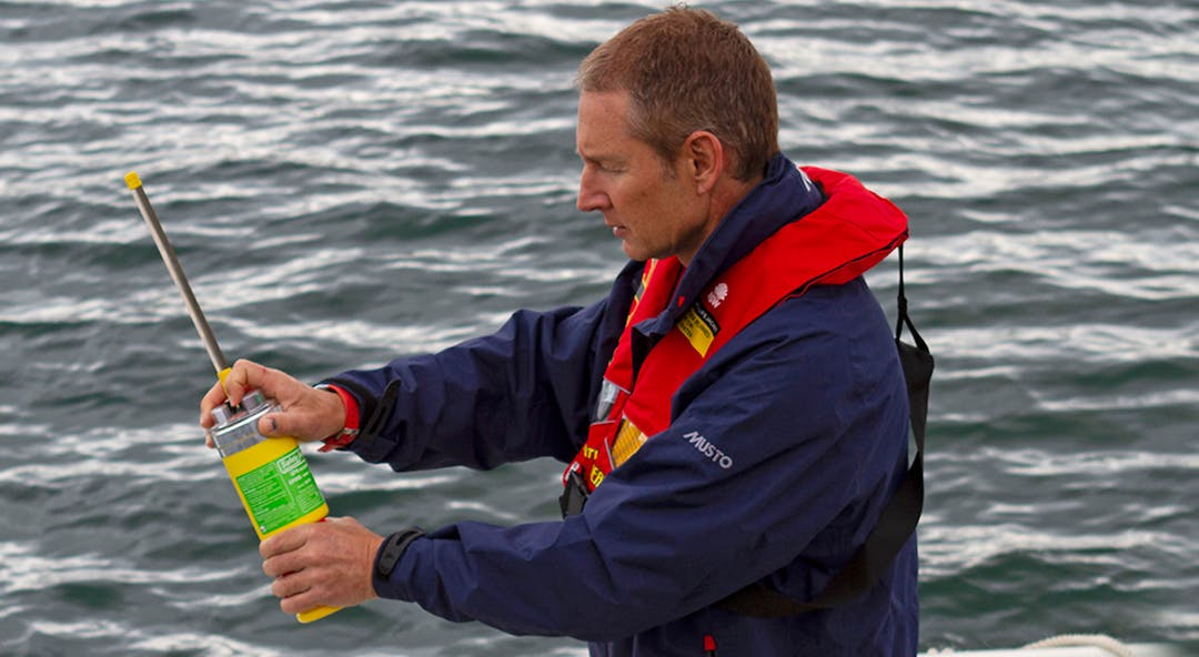 Man on the water wearing life jacket holding an Emergency Position Indicating Radio Beacon.