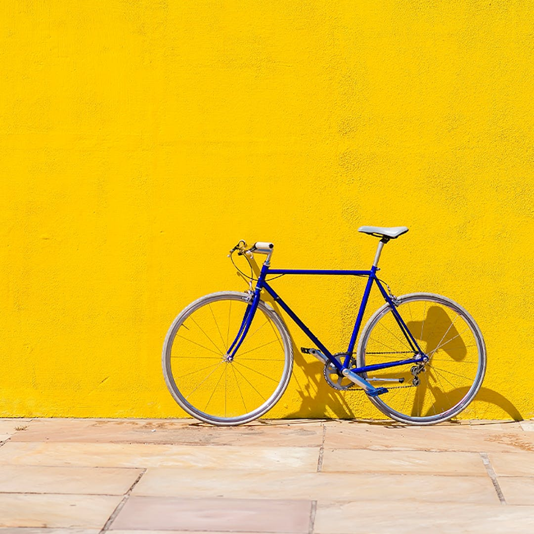 A bicycle in front of a yellow wall.