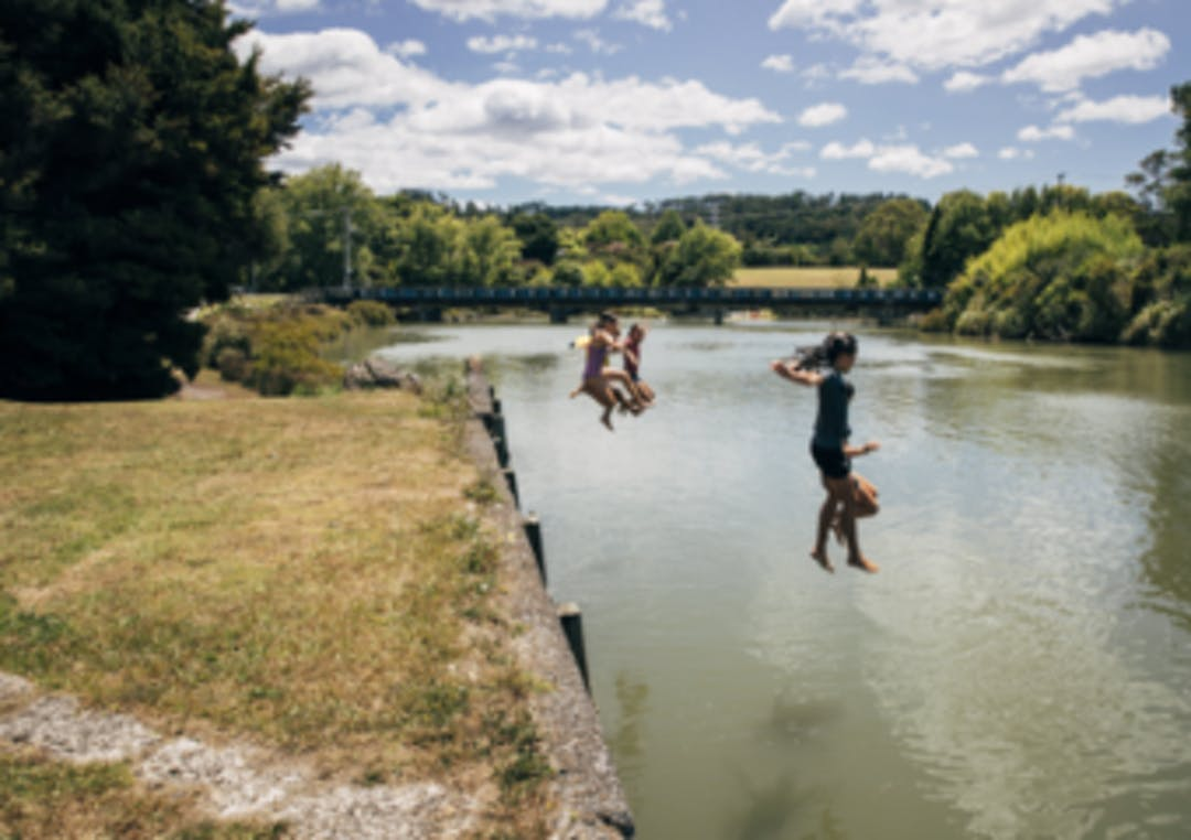 Children jumping into the river on a summer day