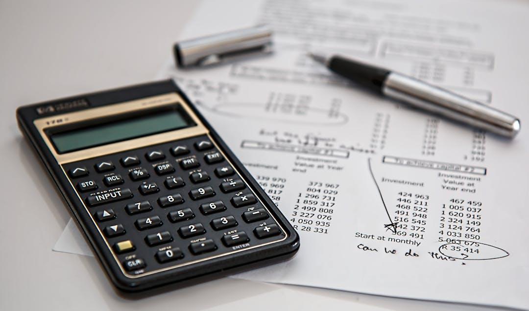 Black calculator near ballpoint pen on white printed paper 53621