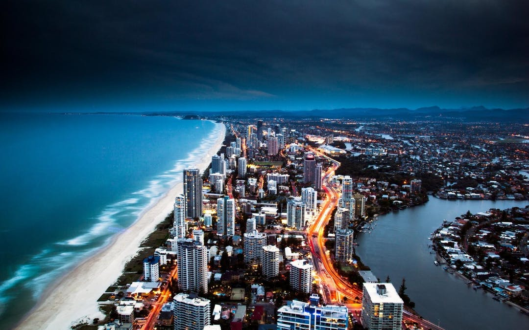 Night view over Gold Coast looking south with beach, high rise buildings, canals and arterial road