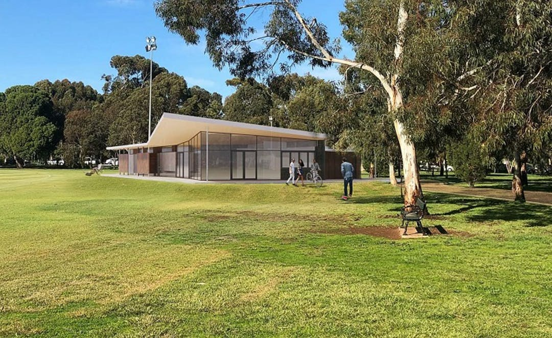 View of Bundey's Paddock/Tidlangga (Park 9) community sports building. You can see a cricketer with a young woman and a person on a bicycle in front of the building. There are trees in the foreground. The building is set amongst the trees and the lush green grass of the park.