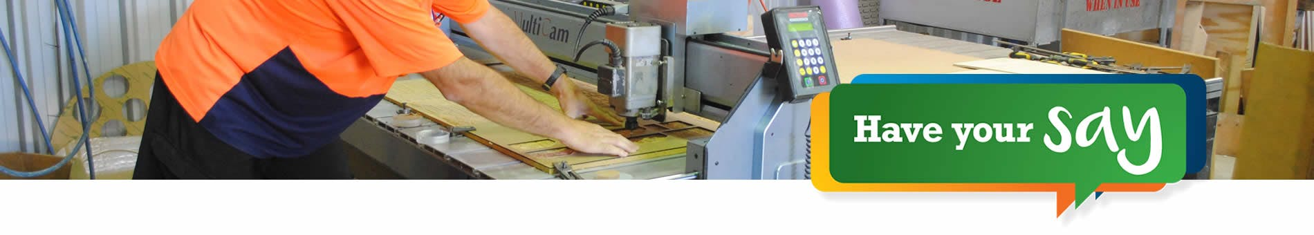 Worker using a planer to cut timber