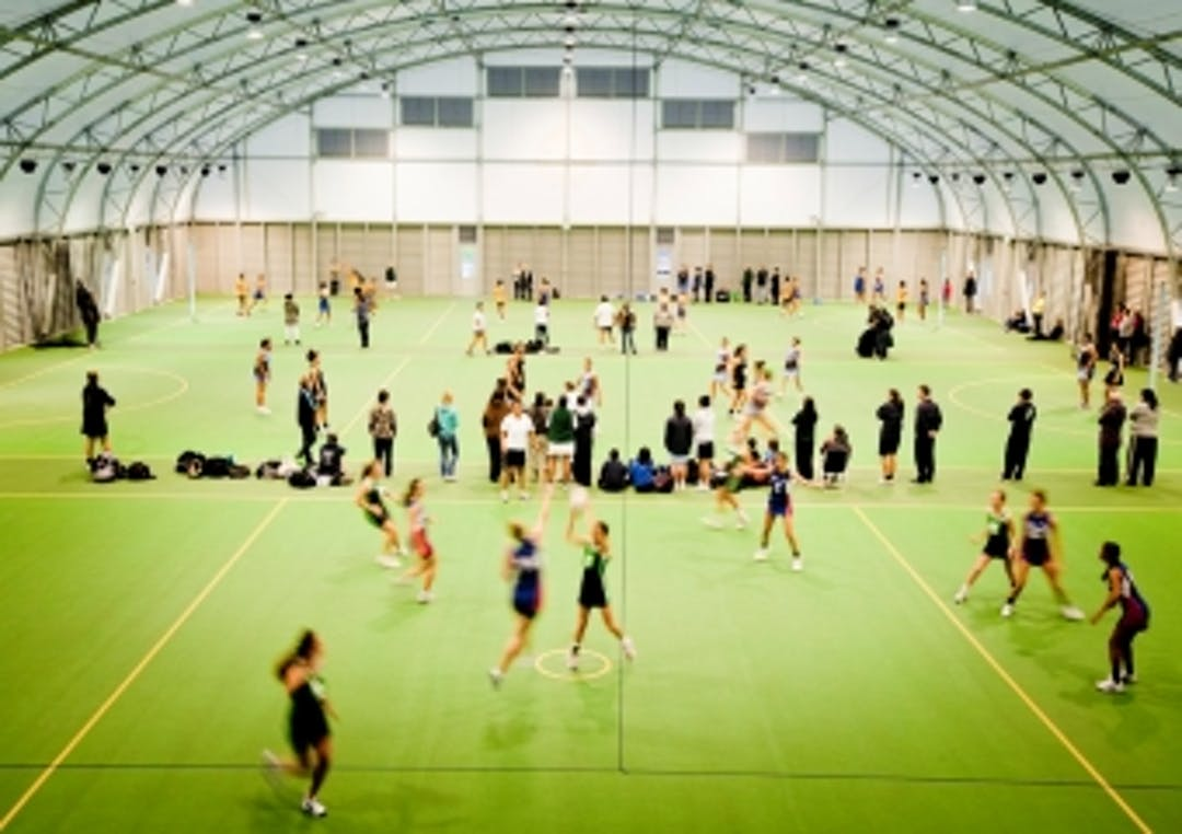 An indoor recreation facility with many people playing and watching indoor sports.