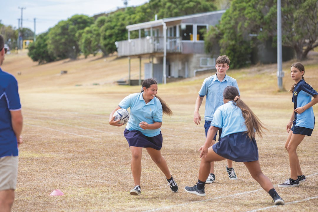 Schoolchildren playing rugby on sports field