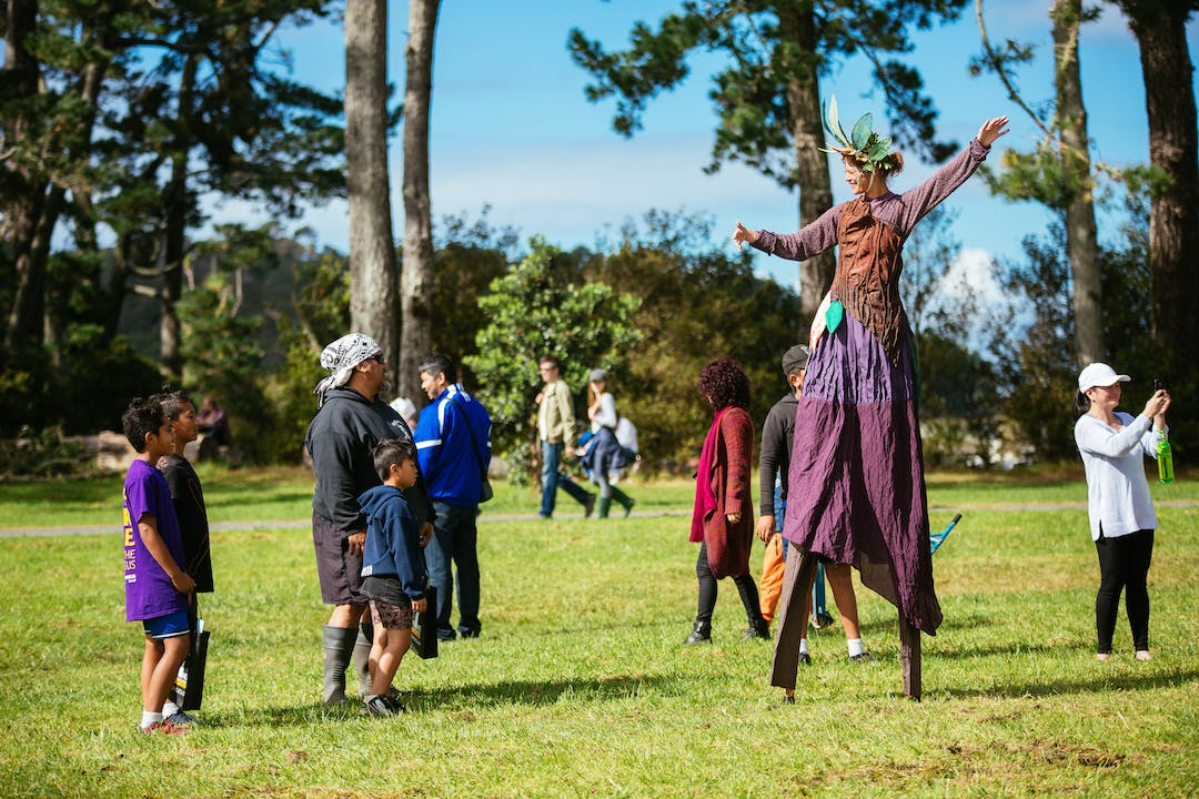Family watching performer on stilts during Kauri Karnival