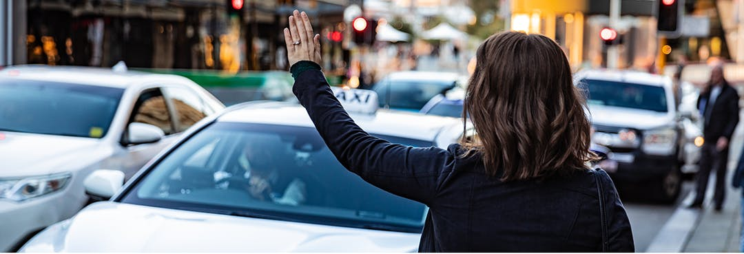 Photo of a woman hailing a taxi. The woman is standing in the foreground and the taxi is blurred in the background.