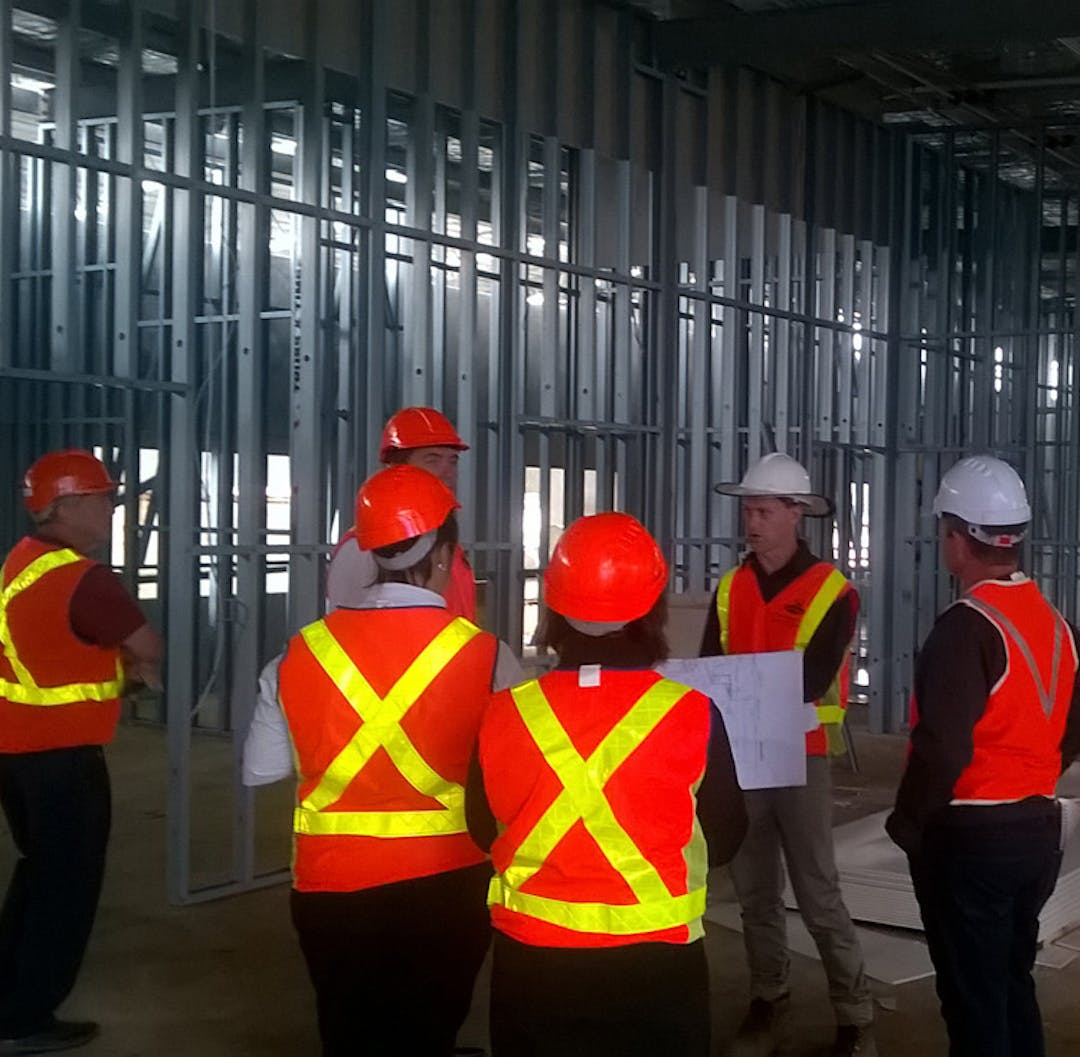 Six workers wearing high visibility vests and hard hats are standing inside a stadium being constructed.