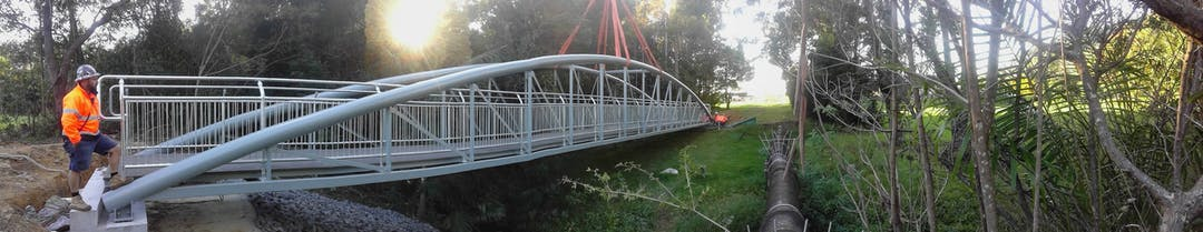 The new bridge is placed into position to link West Coffs District Park in William Sharp Drive with access to Loaders Lane to the east.