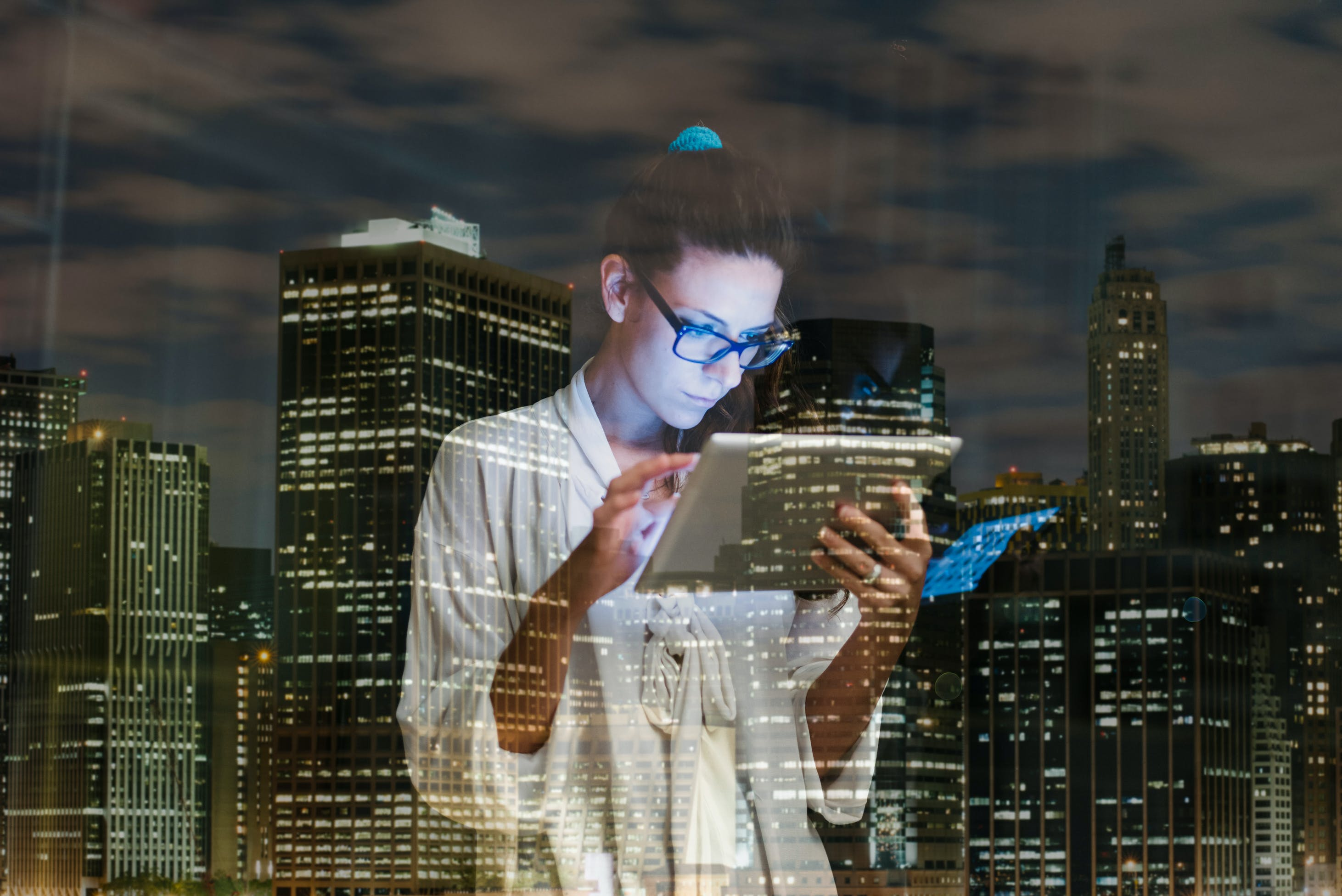 Photo: Female looking at tablet with city background